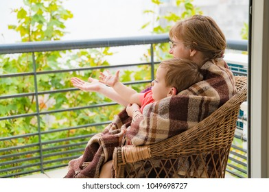 happy grandmother with her grandson on the balcony on a rainy day