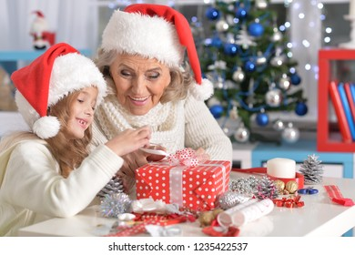 Happy grandmother and her little granddaughter preparing for Christmas together at home