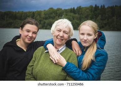 Happy grandmother and her two granddaughters. Outdoors portrait. Autumn, cloudy weather