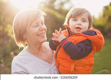A happy grandmother holds a beloved grandson in her arms and smiles
