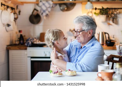 Happy grandmother is hugging granddaughter in cozy home kitchen. Senior woman and cute little child girl are smiling. Kid is enjoying kindness, warm hands, care, support. Family is cooking together.