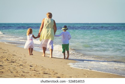 Happy grandmother with kids- little boy and girl- at beach