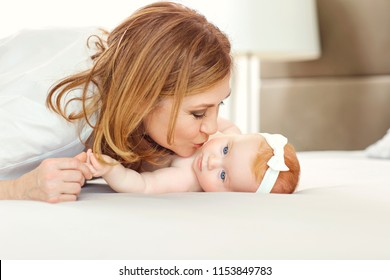 A happy grandmother kissing baby grandson on the bed.