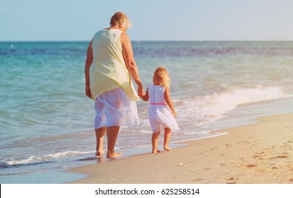 Happy grandmother with little girl walk at beach