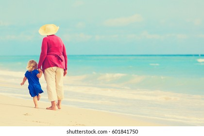 Happy grandmother with little granddaughter walk at beach