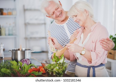 Happy grandmother mixing a salad and her smiling husband hugging her