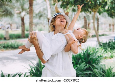 Happy grandmother playing and lifting up her little 3 year old granddaughter