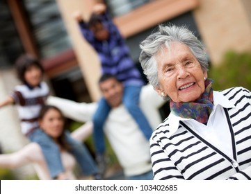 Happy grandmother smiling with her family at the background