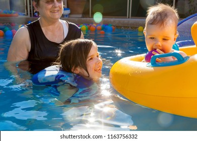 A happy grandmother swims with two of her grandchildren.  The young girl smiles up at her baby brother who is chewing on a plastic ball as he sits in a floatation device. He has Ptosis.