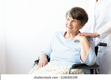 Happy grandmother in a wheelchair and caregiver supporting her. Copy space on the wall