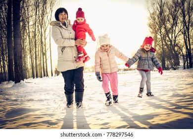 Happy grandmothers enjoying their grand children outside in winter - family portrait.