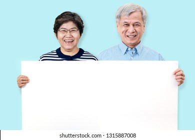 Happy grandpa and grandma smiling with white teeth, enjoy moment and holding a blank board. Asian grandparents showing white blank board for your advertising text message or promotional content.