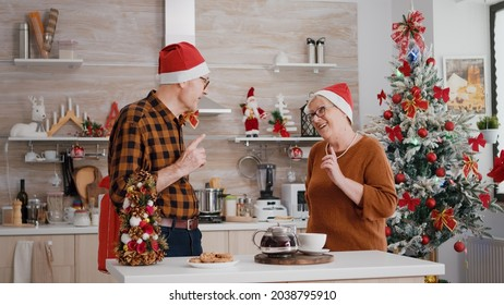 Happy grandparents couple family sharing wrapper gift with ribbon on it enjoying christmastime. Family celebrating winter holiday season surprinsing with present in decorated kitchen
