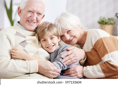 Happy grandparents embracing their smiling grandson, sitting at bright interior