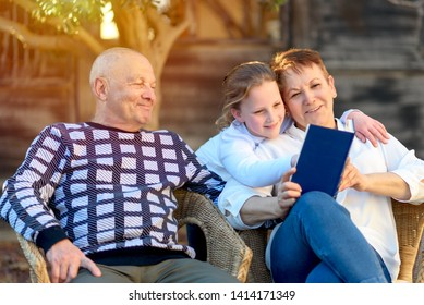 Happy Grandparents Enjoying Their Grandchild Outside. Family Portrait. Beautiful Happy Grandmother and Grandfather Reading to Granddaughter Book in Nature at Sunset.