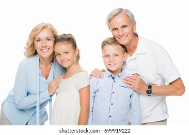 happy grandparents with grandchildren embracing and smiling at camera isolated on white