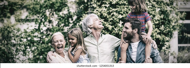 Happy grandparents with grandchildren and son standing in yard