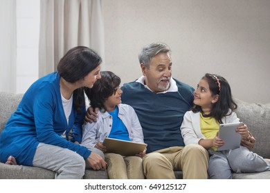 Happy grandparents and grandchildren using digital tablet sitting on sofa