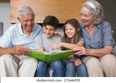 Happy grandparents and grandkids looking at album photo in the living room