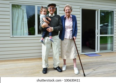 Happy grandparents holding their granddaughter outside their retirement home.Concept photo of grandparents, ,grandchild, childhood,relationship, lifestyle,family. Real people. Copy space