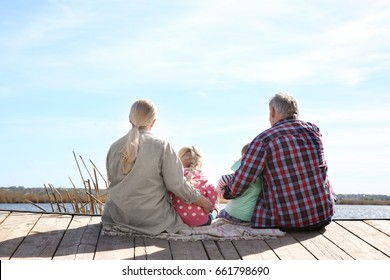 Happy grandparents with little children near river on sunny day