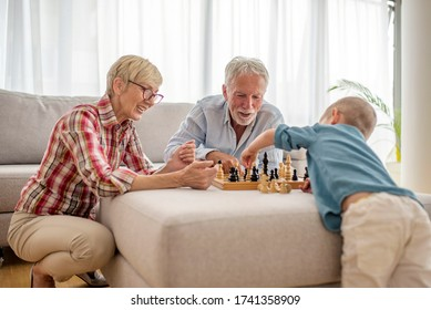 Happy grandparents playing chess with their grandson at home