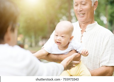 Happy grandparents playing with their grandchild at outdoor park, Asian family, life insurance concept.