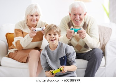 Happy grandparents playing video games with their grandson