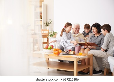 Happy grandparents showing photo album to their grandchildren in a living room