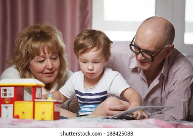 Happy grandparents spending time with their cute grandson playing with puzzle book