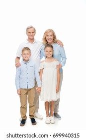 happy grandparents standing with grandchildren and looking at camera, isolated on white