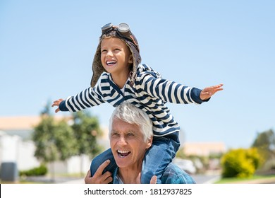 Happy grandson sitting on the shoulders of his grandfather and playing. Grandpa giving young boy piggyback ride outdoors while having fun together. Little kid with pilot helmet and arms outstretched.