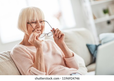 Happy granny. Beautiful senior woman putting on her eyewear while relaxing on the couch at home