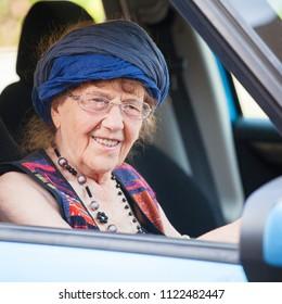 Happy granny at car. Old woman driving. Seniors