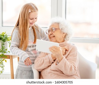 Happy granny with granddaughter using tablet at home