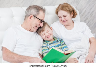 Happy granparents  read the book to her grandson before going to bed
