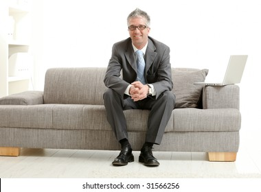 Happy gray haired businessman sitting on couch, looking at camera, smiling.