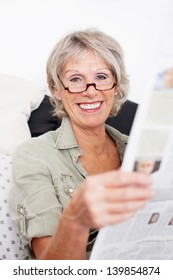 Happy grey haired senior retired woman wearing spectacles sitting reading the newspaper with a big smile of appreciation on her face