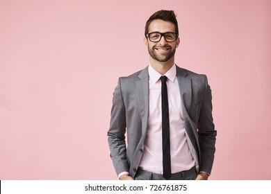 Happy grey suit guy in pink studio, portrait