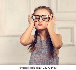 Happy grimacing kid girl in fashion glasses with fun emotional face looking on blue studio background in colorful blouse. Closeup toned portrait