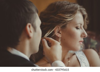happy groom  admires his charming wife