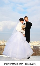 happy groom and bride with bouquet of roses embrace and look at camera at winter outdoors; man talking on phone