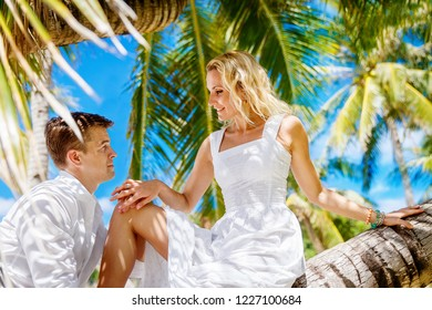 Happy groom and bride having fun in a tropical jungle under the palm tree.  Wedding and honeymoon on a tropical island. Summer vacation concept.