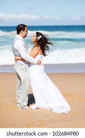 happy groom and bride hugging on beach