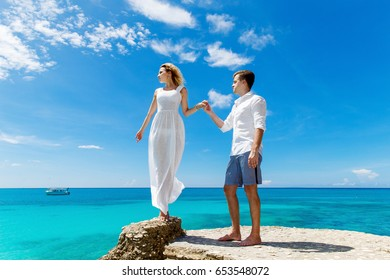 Happy groom and bride on the rock. Turquoise sea in the background. Wedding and honeymoon in tropics concept.
