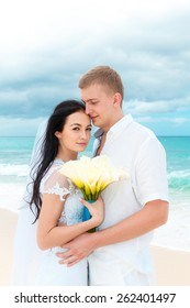 Happy groom and bride on the sandy tropical beach. Wedding and honeymoon concept.