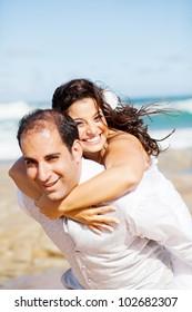 happy groom and bride piggyback on beach