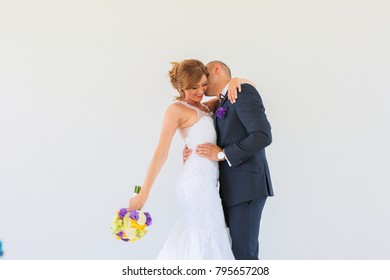 happy groom and bride posing on white background