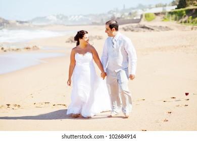 happy groom and bride walking on beach
