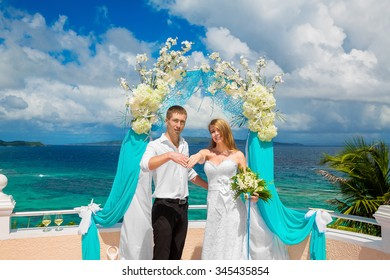 Happy groom and bride with wedding rings under the arch decorated with flowers on the hotel in tropics. Wedding ceremony on a tropical beach in blue. Wedding and honeymoon concept.